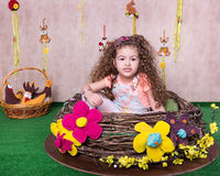 Gullig liten söt flicka i en påskgarnering hemma Arkivbilder