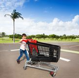 Gullig liten shoppare med den tomma vagnen p? parkeringsplatsen royaltyfri bild