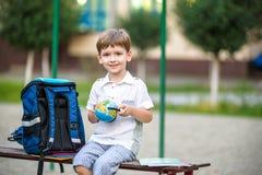 Gullig liten skolpojke som utomhus studerar på solig dag Royaltyfria Foton