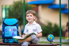 Gullig liten skolpojke som utomhus studerar på solig dag Royaltyfri Foto