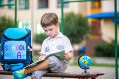 Gullig liten skolpojke som utomhus studerar på solig dag Arkivfoto