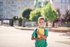 Gullig liten skolpojkedet fria på solig dag Barn med hans ryggsäcken och rymmaböcker royaltyfria foton