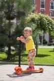 Gullig liten sparkcykel för litet barnflickaridning i staden, ungesport vertikalt Royaltyfria Foton