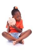 Gullig liten svart flicka som rymmer en le spargris - afrikan ch Arkivfoto