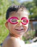 Gullig liten unge med skyddsglasögon som skrattar i pöl Fotografering för Bildbyråer