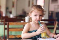 Gullig liten ungeflicka som dricker fruktsaft i kafé Arkivbilder