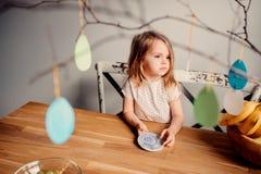 Gullig litet barnflicka hemma med easter garneringar Arkivbild