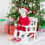 Gullig litet barnflicka i röd klänning och den santa hatten nära julgranen Arkivbilder