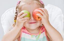 Gullig litet barnflicka med äpplen Royaltyfri Bild