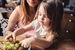 Gullig litet barnflicka som äter druvor med modern på köket royaltyfria foton