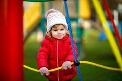 Gullig litet barnflicka som har gyckel p? lekplats Lyckligt sunt litet barn som kl?ttrar, sv?nger och glider p? olikt royaltyfri bild