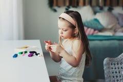 Gullig litet barnflicka som hemma spelar med plasticine eller lekdeg Royaltyfri Fotografi