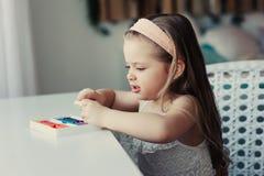 Gullig litet barnflicka som hemma spelar med plasticine eller lekdeg Royaltyfria Bilder