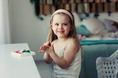Gullig litet barnflicka som hemma spelar med plasticine eller lekdeg Fotografering för Bildbyråer