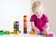 Gullig litet barnflicka som plaing med färgrika kvarter Fotografering för Bildbyråer