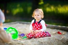 Gullig litet barnflicka som spelar i sand på utomhus- lekplats Härligt behandla som ett barn i byxa för rött gummi som har gyckel royaltyfri foto