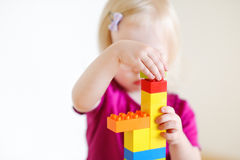 Gullig litet barnflicka som spelar med färgrika kvarter Royaltyfri Fotografi