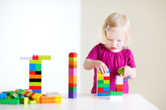 Gullig litet barnflicka som spelar med färgrika kvarter Arkivbild
