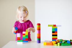 Gullig litet barnflicka som spelar med färgrika kvarter Royaltyfria Foton