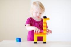 Gullig litet barnflicka som spelar med färgrika kvarter Royaltyfri Foto