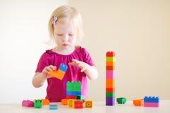 Gullig litet barnflicka som spelar med färgrika kvarter Arkivfoton