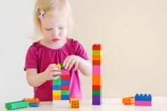 Gullig litet barnflicka som spelar med färgrika kvarter Fotografering för Bildbyråer