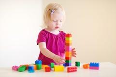 Gullig litet barnflicka som spelar med färgrika kvarter Royaltyfria Bilder