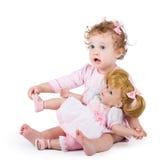 Gullig litet barnflicka som spelar med hennes första docka Arkivfoton