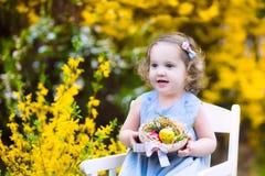Gullig litet barnflicka som tycker om jakt för easter ägg i trädgård arkivbilder