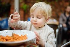 Gullig litet barnpojke som inomhus äter pasta i restaurang för italienare royaltyfri fotografi
