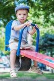 Gullig litet barnpojkeridning på en gunga arkivbilder