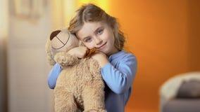 Gullig lockig-haired blond flicka som kramar nallebjörnen och ler på kameran, lycka fotografering för bildbyråer