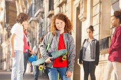 Gullig lockig-haired tonårs- pojke med skateboarden Arkivbilder