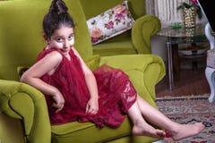 Gullig lovlely mitt - östlig flicka med mörker - röd klänning och samlat hår som poserar och liying på hemmastadd inre för grön s arkivfoton