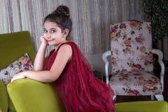 Gullig lovlely mitt - östlig flicka med mörker - röd klänning och samlat hår som poserar och liying på hemmastadd inre för grön s arkivbild