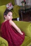 Gullig lovlely mitt - östlig flicka med mörker - röd klänning och samlat hår som poserar och liying på hemmastadd inre för grön s royaltyfria foton