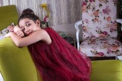 Gullig lovlely mitt - östlig flicka med mörker - röd klänning och samlat hår som poserar och liying på hemmastadd inre för grön s arkivbilder