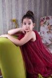 Gullig lovlely mitt - östlig flicka med mörker - röd klänning och samlat hår som poserar och liying på hemmastadd inre för grön s royaltyfria bilder