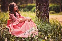 Gullig lycklig barnflicka i sagaprinsessaklänning på gå i sommar Arkivfoto