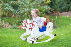 Gullig lycklig flicka på att vagga hästen i trädgården arkivfoto