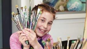 Gullig lycklig flicka som ler till kamerainnehavgruppen av målarpenslar arkivfilmer