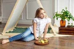 Gullig lycklig liten flicka med blont hår i en vit skjorta och jeansdrömmar som sitter på golvet nära tältet royaltyfri foto