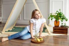 Gullig lycklig liten flicka med blont hår i en vit skjorta och jeansdrömmar som sitter på golvet nära tältet royaltyfria foton