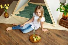 Gullig lycklig liten flicka med blont hår i en vit skjorta och jeansdrömmar som sitter på golvet nära tältet fotografering för bildbyråer