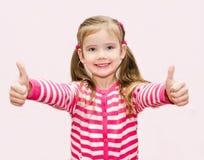 Gullig lycklig liten flicka med tummar upp royaltyfria foton