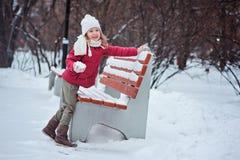 Gullig lycklig liten flickadanande kastar snöboll på gå i den snöig vintern parkerar Royaltyfri Bild