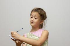 Gullig lycklig liten flickahandstil något i hennes anteckningsbok Royaltyfri Fotografi