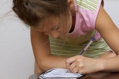 Gullig lycklig liten flickahandstil något i hennes anteckningsbok Royaltyfria Bilder
