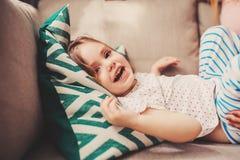 Gullig lycklig litet barnflicka som har gyckel hemma Arkivbilder