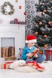 Gullig lycklig pojke i den santa hatten med leksakjulgåvor Arkivbild
